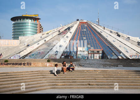 People sitting on the steps of the graffiti-covered The Pyramid International Center of Culture with glass high - Stock Photo