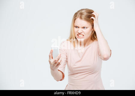 Angry woman using smartphone isolated on a white background - Stock Photo