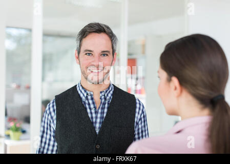 Portrait of a forty years old man with grey hair and beard wearing a checkered blue shirt. A woman with a pink shirt - Stock Photo