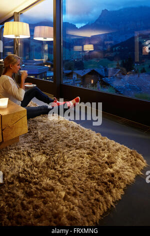 Woman sitting on floor in a hotel winter garden while enjoying view in the evening, Adelboden, Canton of Bern, Switzerland - Stock Photo