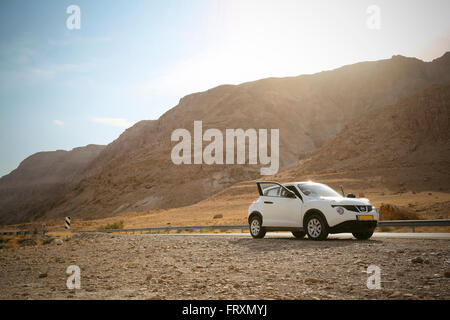 Isreal, parked car at the roadside in the desert near Dead Sea - Stock Photo