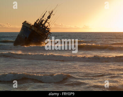 Shipwreck at sunset at Laayoune Plage, Western Sahara, Southwest Morocco - Stock Photo