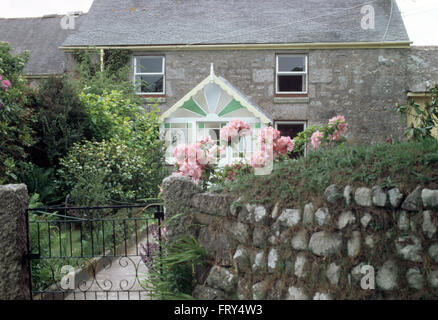 Pink roses beside wall with wrought iron gate in front garden of a stone cottage with a Victorian glass porch - Stock Photo