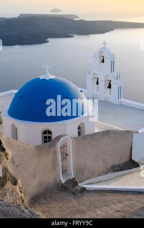 view of a typical church in White and Blue and the caldera at sunset on the island of Santorini Greece - Stock Photo