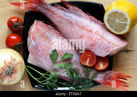 Two raw groupers ready for cooking on wooden board - Stock Photo