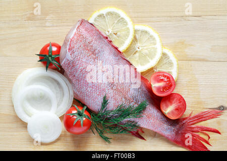 Raw grouper ready for cooking near vegetables on wooden board - Stock Photo