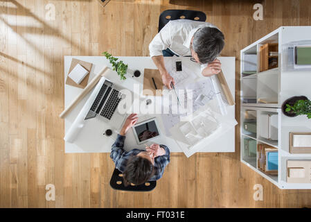 Top view at office. Two architects, a man and a woman, sitting at a desk and working on a project. Focus on the - Stock Photo