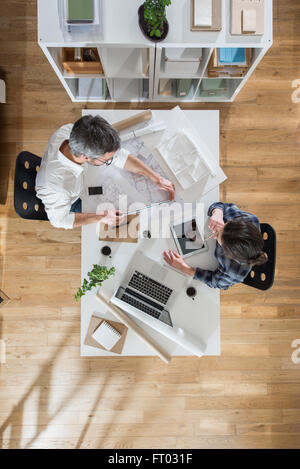 Top view at office. Two architects, a man and a woman, sitting at a desk and working on blueprints. Focus on the - Stock Photo