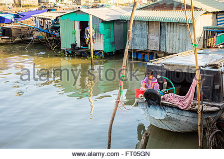 A Vietnamese woman washes clothes on a houseboat in a floating village on a branch of the Mekong River, Can Tho, Vietnam