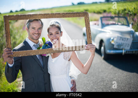 charming bride and groom playing with a frame for their wedding photos ft05k2