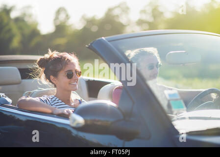 Young couple in his convertible car, happy to drive on a country road, focus on the woman. Shot with flare - Stock Photo
