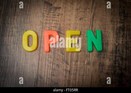 Open, spelt out in multi coloured fridge magnet letters - Stock Photo
