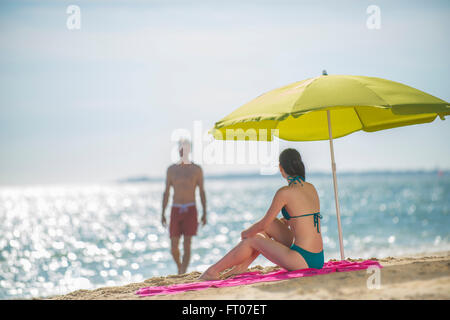 handsome couple in swimsuit at the beach the female sitting under a beach umbrella watchs her man coming back from - Stock Photo