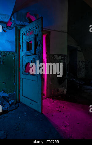 Abstract colorful light painting in abandoned soviet bunker. Pink bright light through broken doors - Stock Photo