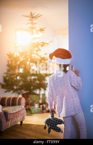Christmas morning, a little girl in pajamas, wearing a Santa Claus hat opens the living room door and discovers - Stock Photo