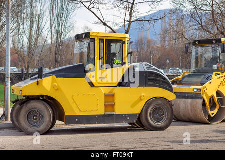Road construction vehicles, yellow road roller. - Stock Photo