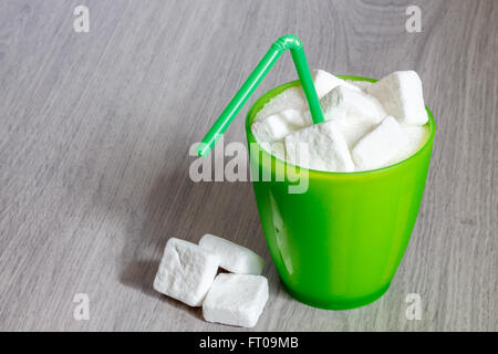 Green plastic glass with straw full of sugar and sugar cubes. Concept image for too much sugar in sodas, juices, - Stock Photo