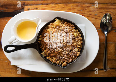 Apple crumble served with a pot of custard in London, England. - Stock Photo