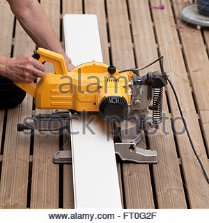 Man working with miter saw - Stock Photo