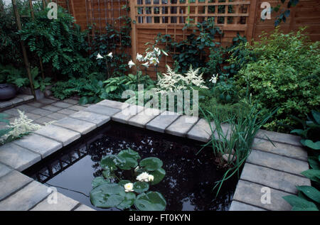 Waterlilies in pool edged with stone paving in small town garden with white astilbe and lilies - Stock Photo