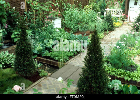 Box Pyramids Either Side Of A Paved Path In Small Well Maintained Vegetable Garden
