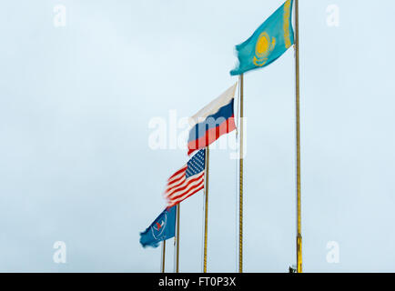 Flags of the U.S., Russia, Roscosmos, and Kazakhstan are seen blowing in the high winds that delayed operations - Stock Photo