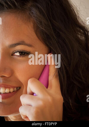Smiling young Hispanic woman using cell phone - Puerto Vallarta, Mexico  #613PV - Stock Photo