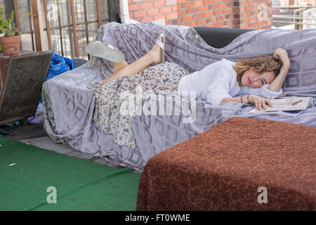 Young Woman Resting on Couch in Terrace in the Afternoon
