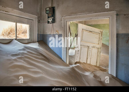 Door and electricity meter surrounded by sand dunes, interior of the deserted ghost town in the Diamond restricted - Stock Photo