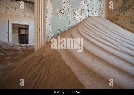 Sand dune burying the interior of a house in the deserted ghost town in the Diamond restricted area, Kolmanskop - Stock Photo
