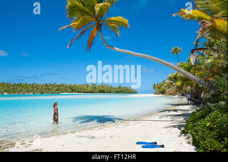 Woman strolling along the beach with palm trees at One Foot Island in Aitutaki Lagoon, Aitutaki, Cook Islands, South - Stock Photo