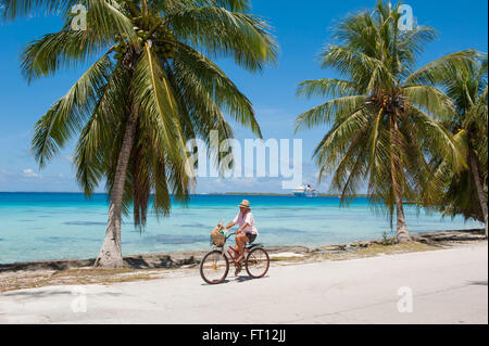 Man riding his bicycle along a road with palm trees, expedition cruise ship MS Hanseatic Hapag-Lloyd Cruises at - Stock Photo