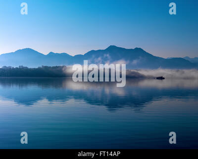 Herreninsel and mountains Hochfelln and Hochgern in morning fog, lake Chiemsee, Bavaria, Germany - Stock Photo