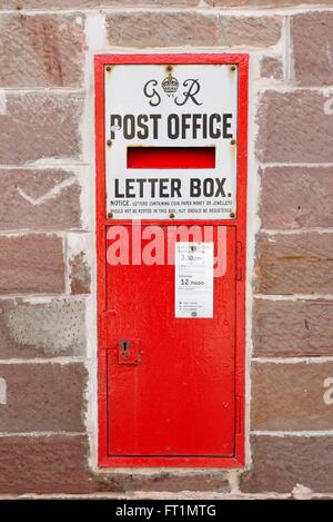 GR vi (six) wall mounted post office letter box in British red colouring at the general store in Luss, Scotland, - Stock Photo