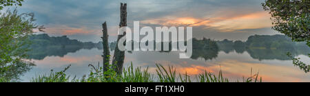 Panoramic scene of Attenborough nature reserve at sunset reflected in the water. Nottinghamshire, September - Stock Photo