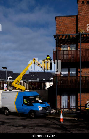 Dublin house service worker repairing the facade of a house using an articulated boom lift van - Stock Photo