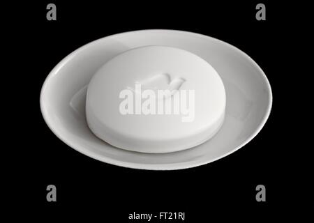 A bar of dove soap in a white dish - Stock Photo