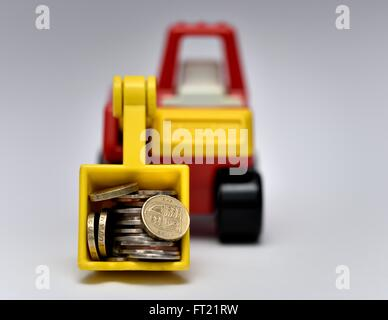 A toy digger carrying coins - Stock Photo