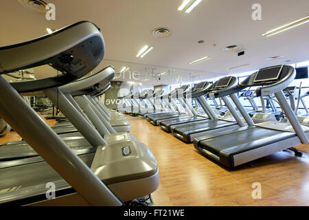 Rows of vacant treadmills at an empty gym - Stock Photo