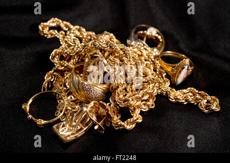 scrap gold jewellery including chains, bracelets and rings on a black background - Stock Photo