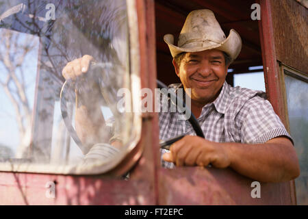 Farming and cultivations in Latin America. Portrait of middle aged hispanic farmer sitting proud in his tractor - Stock Photo