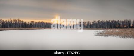 early spring morning. Lake still under snow - Stock Photo