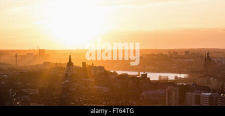 Panoramic view of residential district against orange sky during sunset - Stock Photo