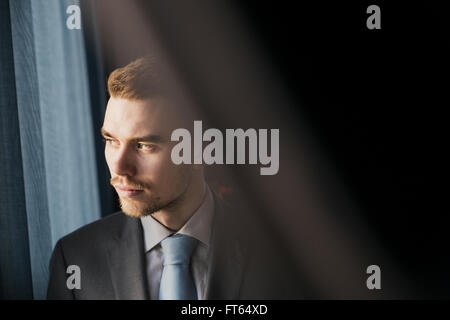 Thoughtful businessman looking through window at hotel room - Stock Photo