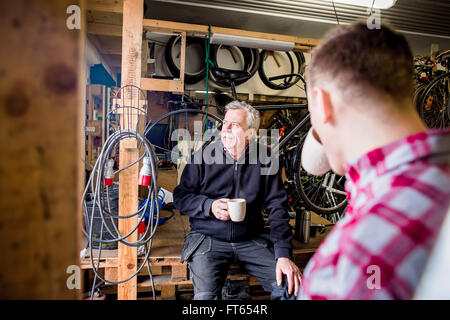 Father and son drinking coffee at bicycle shop - Stock Photo