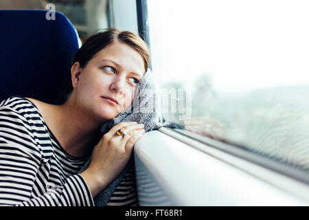 Thoughtful businesswoman looking out through train window - Stock Photo