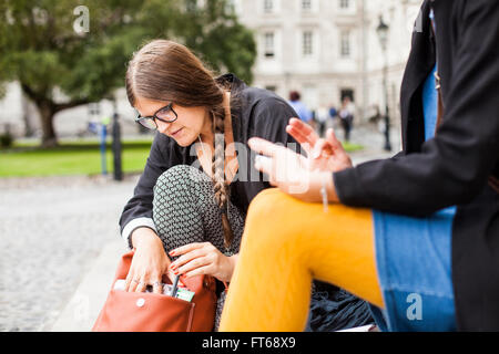 Woman searching something in bag while sitting with friend on steps - Stock Photo