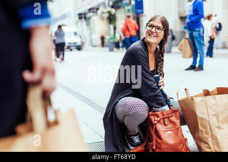 Happy woman looking at female friend while searching something in bag at city street - Stock Photo