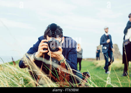 Man photographing through SLR camera on hill against sky - Stock Photo