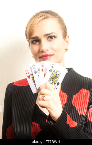 Pretty young woman holding playing cards against wallpaper background - Stock Photo